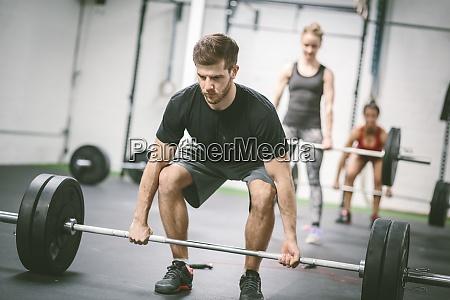 menschen in fitnessstudio gewichte heben