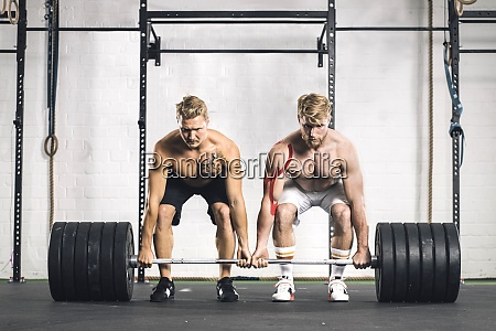 zwei junge maenner im fitnessstudio heben