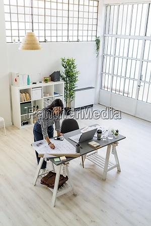 selbstbewusste geschaeftsfrau arbeitet an blueprint am