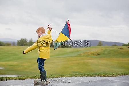 rothaariger kleiner junge mit regenschirm spielt