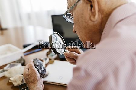 rentner senior maennlich blick durch lupe