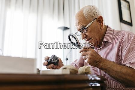 pensionierteseniore maennlich mit lupe fuer die