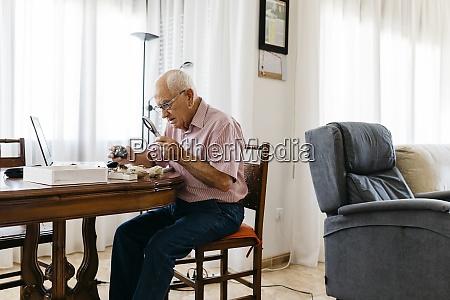 retired, elderly, man, using, magnifying, glass - 29119642