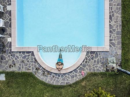 drohnenansicht des mannes entspannenschwimmbad