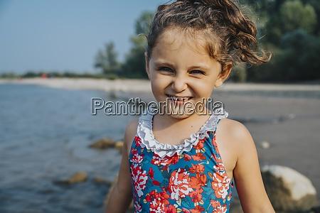 nettes maedchen laechelnd waehrend am strand