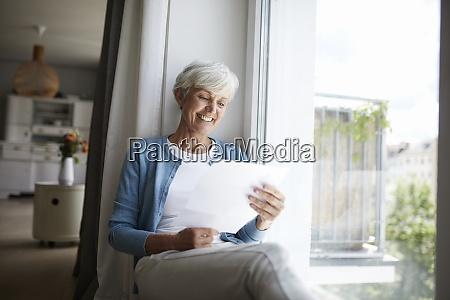 seniorin liest brief gluecklich waehrend sie