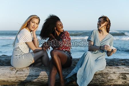 laechelnde freunde sitzen am sonnigen tag