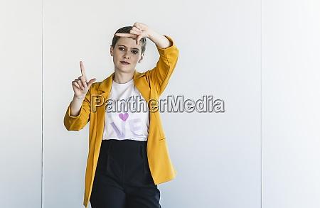 geschaeftsfrau mit gelbem blazer die fingerrahmen