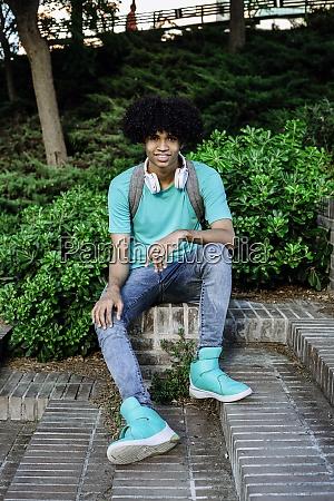 junger mann mit kopfhoerer auf betonbank
