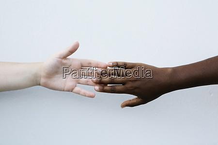 freunde halten hand gegen weisse wand