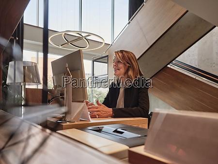 laechelnde seniorin arbeitet am computer im