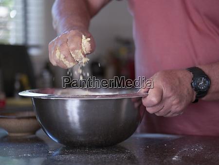 mann mischt zutaten fuer kuchen
