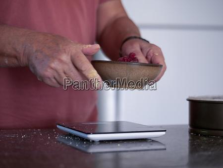 mann wiegt zutaten fuer kuchen
