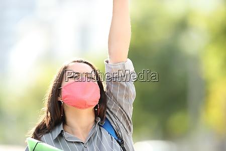 aufgeregte studentin mit maske feiert im