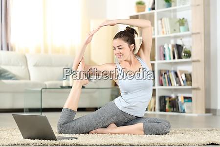 frau zu hause beobachten yoga tutorial