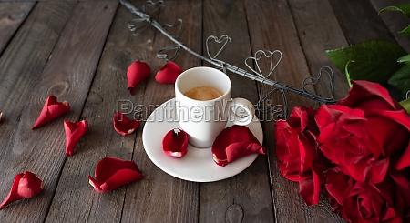 tasse kaffee mit roten rosen und