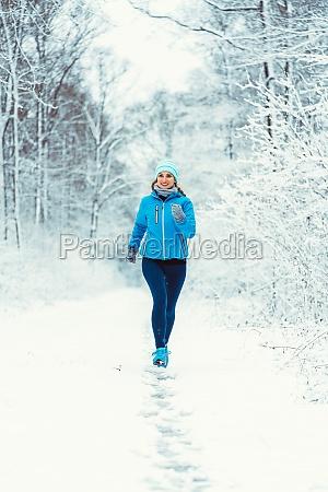 frau joggt in kaltem und verschneitem
