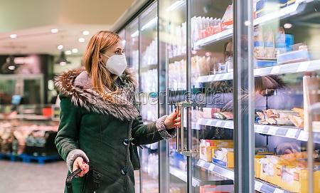 frau im supermarkt tiefkuehltruhen abschnitt traegt