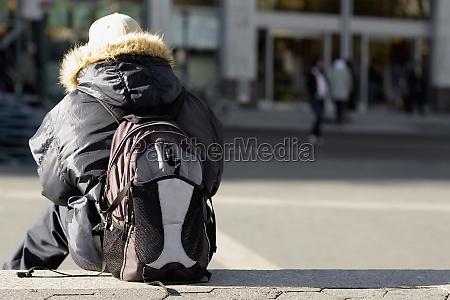 rueckansicht einer person die einen rucksack