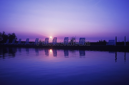 reflection, of, lounge, chairs, in, water, - 29458814