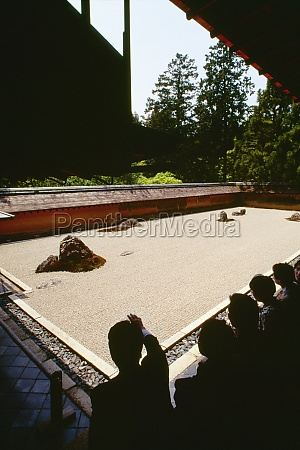 touristen in einem felsengarten ryoanji zen