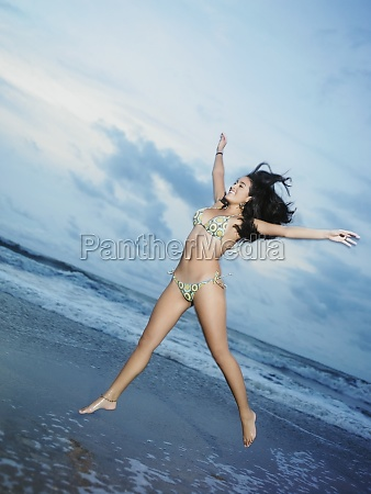 junge frau springt am strand