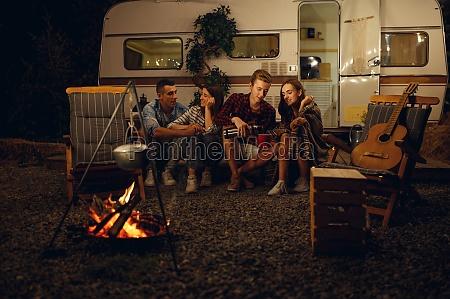freunde sitzen am lagerfeuer in der