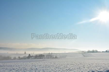 schneelandschaft mit feldern und nebel im