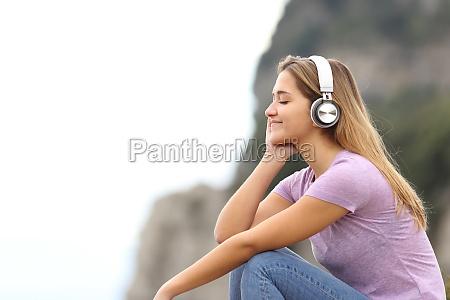 entspannte frau beim musikhoeren im berg