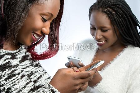 afrikanische teenager maedchen tippen auf smartphones