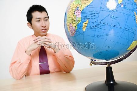 geschaeftsmann mit blick auf einen globus