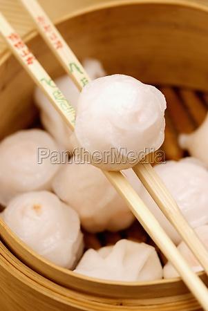 nahaufnahme chinesischer knoedel die in essstaebchen