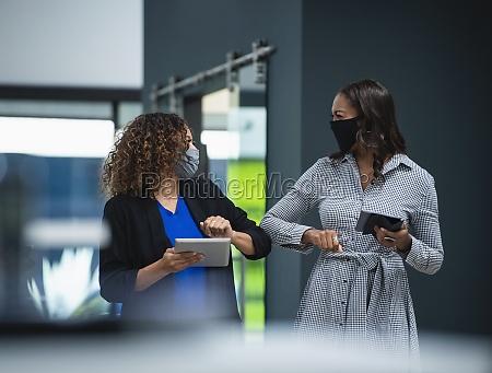 geschaeftsfrauen im gesicht masken gruss mit