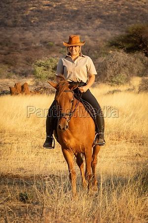 laechelnde blondine auf dem pferd mit