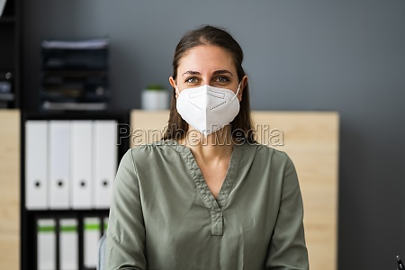 rezeptionistin frau traegt medizinische maske