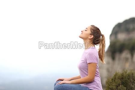 frau sitzt und atmet frische luft