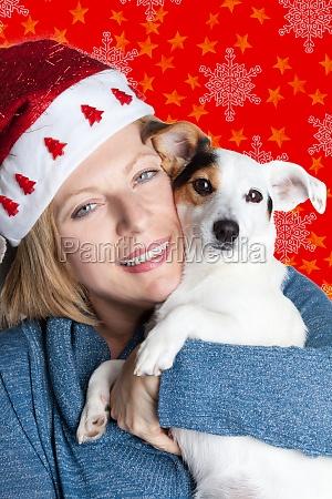 frau mit weihnachtsmuetze umarmt ihren jack
