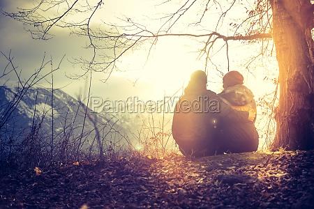 idyllische bergsonnenuntergangskulisse junges sitzpaar geniesst die