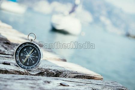 segeln nautischer kompass auf holziger dockpier