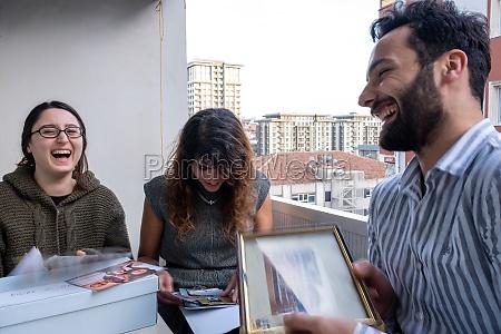 drei freunde lachen beim UEberpruefen alter