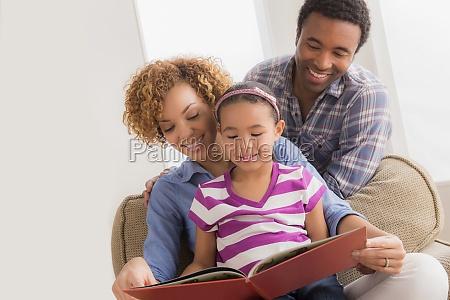 eltern mit tochter lesen buch