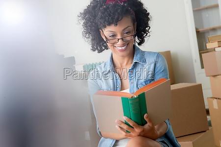 mittlere erwachsene frau lesen buch umgeben
