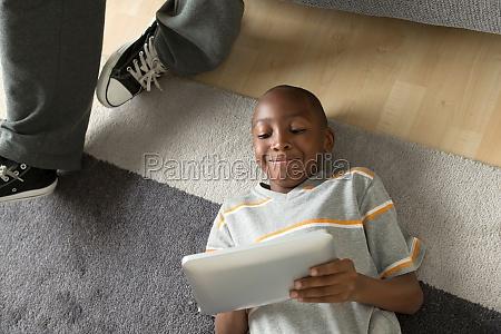 junge liegt mit digitalem tablet auf