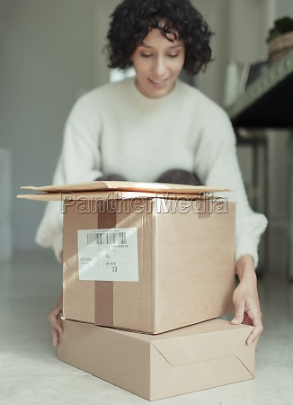 frau erhaelt pakete auf dem boden