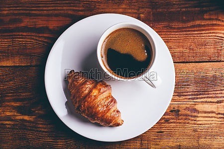 frisches croissant und tasse schwarzen kaffee