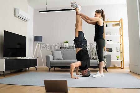 mann macht yoga kopfstand UEbung training