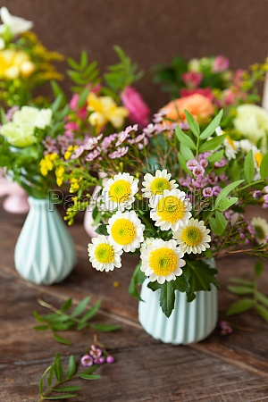 frische fruehlingsblumen in kleinen vasen
