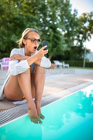 junge schoene sonnengebraeunte frau traegt sonnenbrille