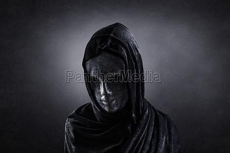 gruselige figur mit kapuzenumhang im dunkeln