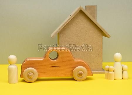 holzhaus und auto mit miniatur familienfiguren